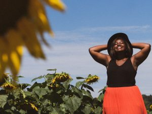 Image of a woman in a field of sunflowers smiling and looking into the sun. This woman represents how free people feel after undergoing EMDR therapy in Pikesville, MD. Often, domestic violence survivors feel empowered after working with an EMDR therapist in Pikesville, MD. 21208