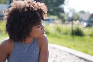 Image of a Black woman looking to her left and into the distance. This photo is representative of how those going through therapy for homicide survivors in Baltimore, MD are able to look forward after working with a trauma therapist in Pikesville, MD. | 21208
