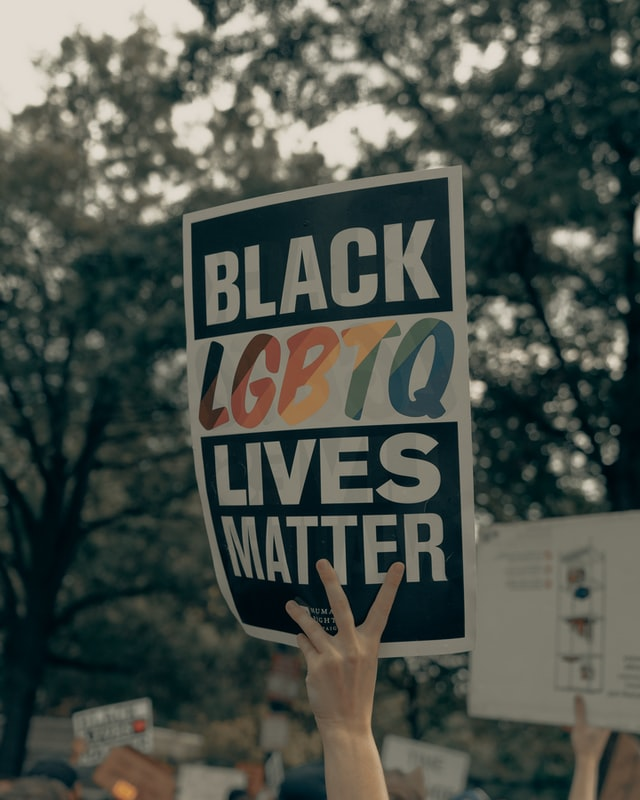 "Photo of a white hand holding up a sign reading ""Black LGBTQ lives matter"" in a protest. This photo is representative of the many Black LGBTQ people who are murdered, leaving their loved ones in need of trauma therapy. Therapy for homicide survivors in Baltimore, MD can help survivors process trauma and heal. 