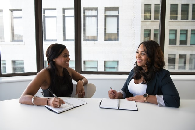 Image of two women at a conference table talking. This image represents what clinical supervision in Maryland may look like for an LMSW meeting with a clinical supervisor in Maryland. 21136