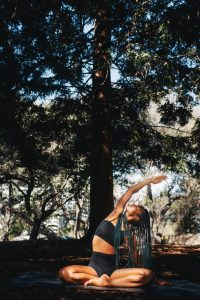 Image of a woman sitting outside near a tree practicing yoga. This image represents the healing that can take place with a holistic therapist during mind-body medicine in Baltimore, MD. 21117