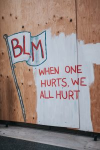 """Image of a wall painted """"BLM When one hurts, we all hurt."""" This image illustrates how the shadow side and traumatic grief impact the Black community. Therapy for homicide survivors in Pikesville, MD can help homicide survivors heal from traumatic grief. 